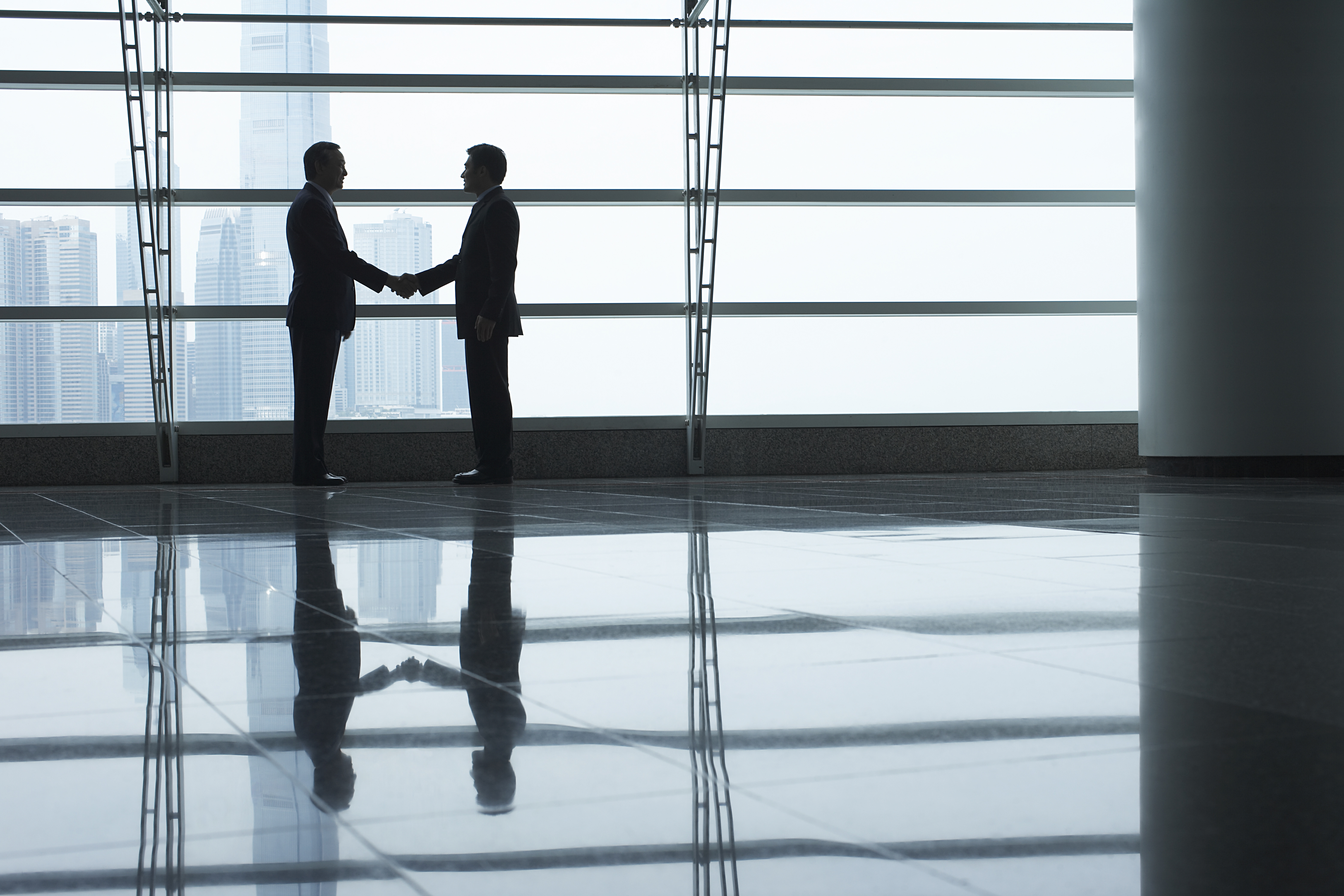 Two men shaking hands in lobby of building