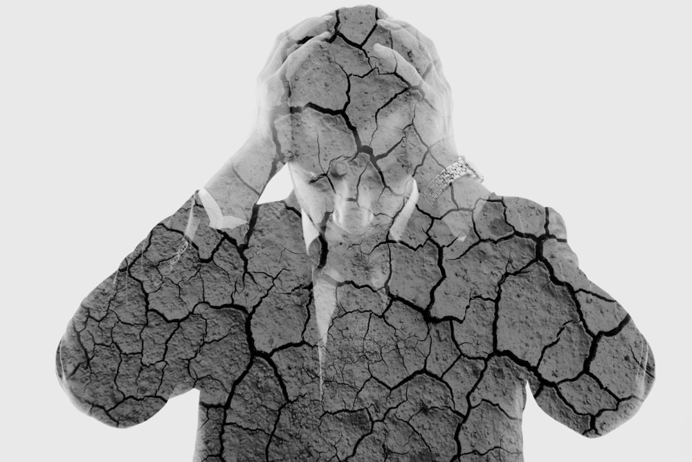 double exposure of depressed business man and dry ground background.jpeg