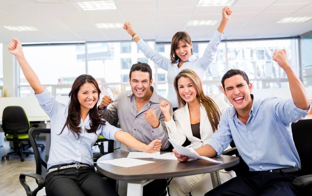 Successful business team with arms up at the office.jpeg