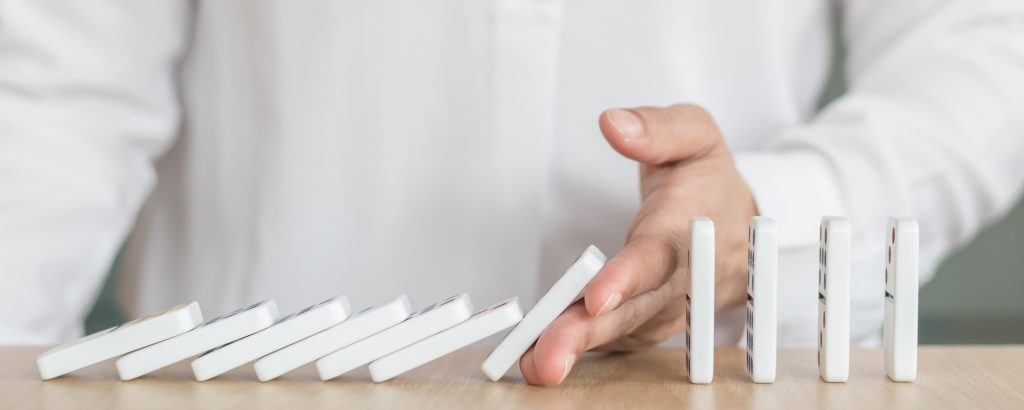 Business solution strategy with stopping domino effect concept for financial or investment protection and successful intervention with corporate person's hand blocking the collapse disruption.