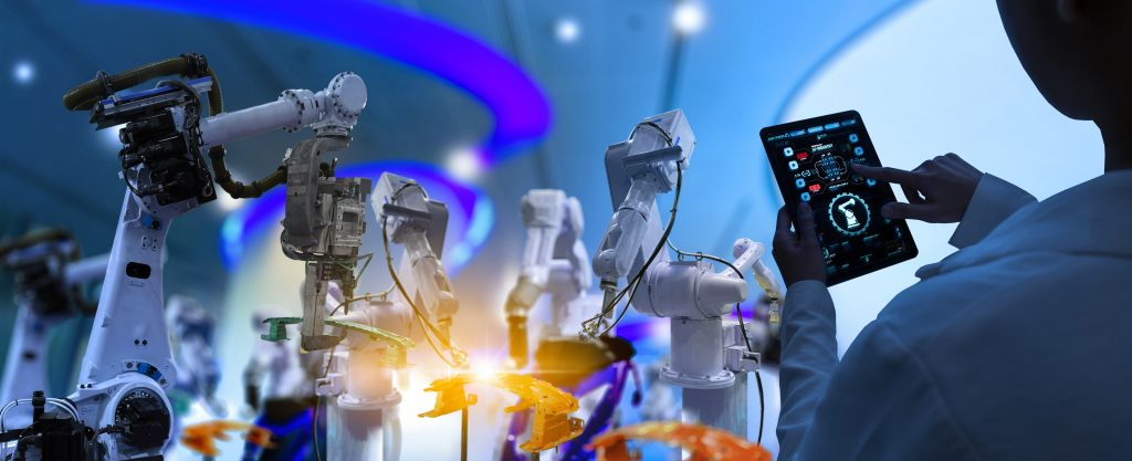 Factory Female Industrial Engineer working with automation robot arms machine in intelligent factory industrial on real time monitoring system software. Digital future manufacture.